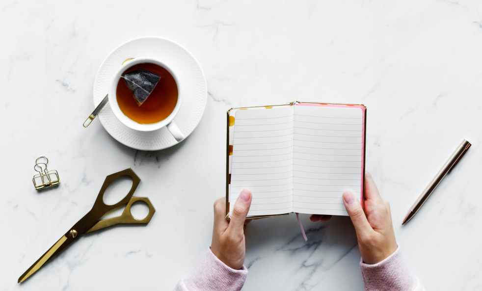 person holding empty book near pen and shears with a cup of tea